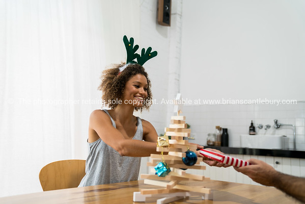 Young woman at table on Christmas table with simple Christmas tree decoration and gifts