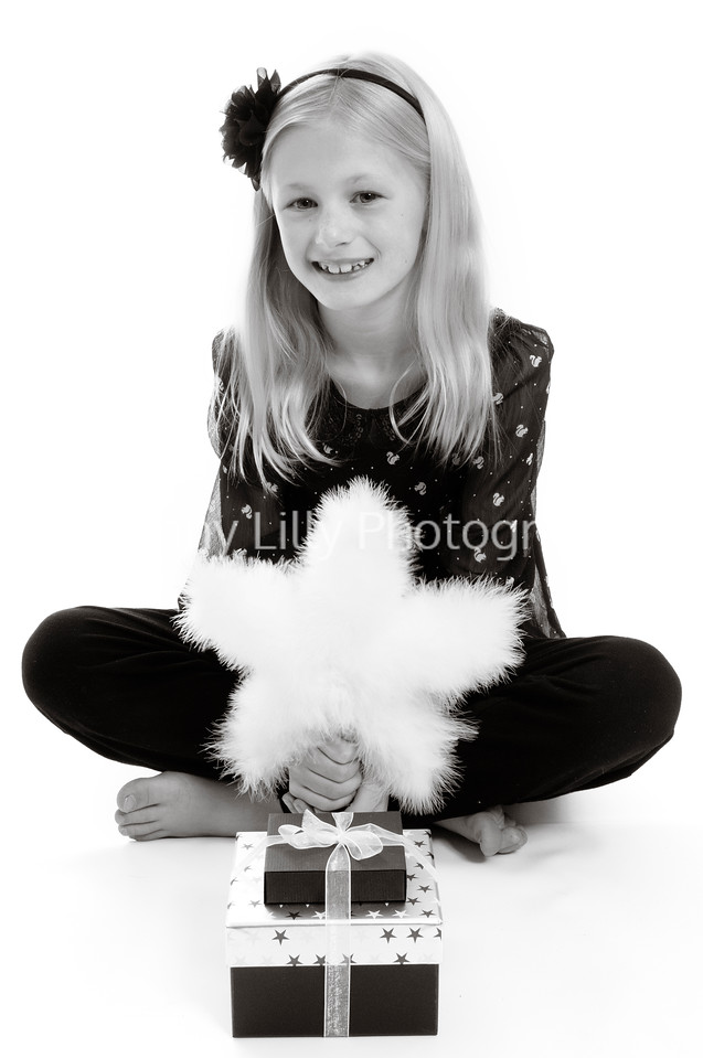 pretty blonde girl with a feather Christmas tree decoration and Christmas presents, isolated on white background