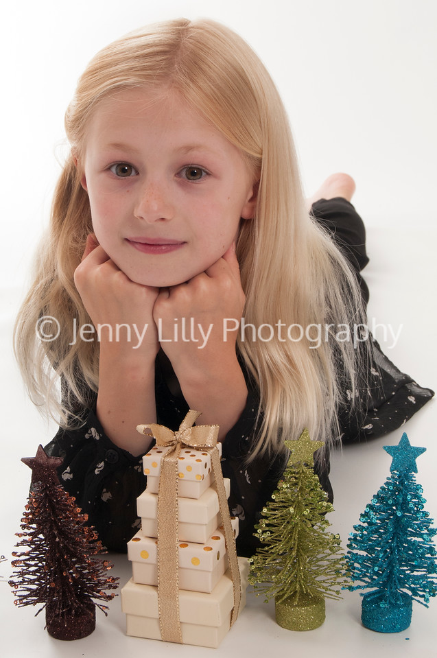 pretty blonde girl lying down with Christmas trees and Christmas presents, isolated on white background