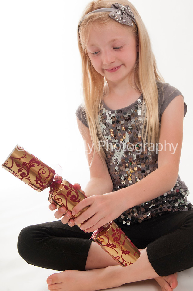 pretty blonde girl with Christmas cracker, isolated on white background