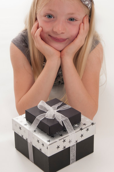 pretty blonde girl lying down with Christmas presents isolated on white background