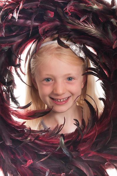 pretty blonde girl peepinng through a feather wreath
