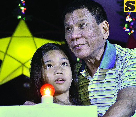 Davao City Mayor Rodrigo Duterte and his daughter Veronica appear in awe while gazing at lighted Christmas decors that sparkle at night as they lead the ceremonial lighting at Rizal Park on Monday evening. (Photo by King Rodriguez of Sun.Star Davao)
