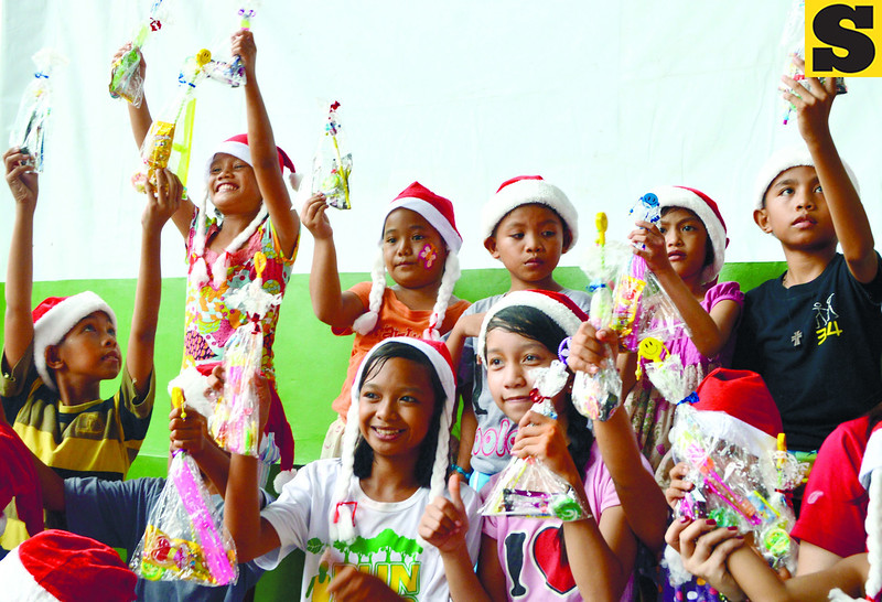 Children-evacuees at the evacuation center in Barangay Tinago, Cebu City get Christmas treats from a group of young Filipinos from Brisbane, Australia who are helping in the reconstruction of houses in north Cebu that were damaged by Typhoon Yolanda. (Alan Tangcawan photo/Sun.Star Cebu)