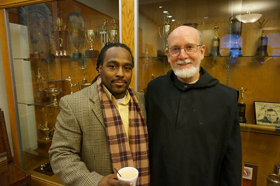 Conschiel McPleasant '93 and Fr. Mark Payne, O.S.B. '69 catch up in the Trophy Room before Convocation.