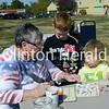 Mona Redman asks Eamon and Cormac Nichols what they would like painted on their faces during the September Showcase on Saturday at the Clinton Public Library's main branch. • Katie Dahlstrom/Clinton Herald