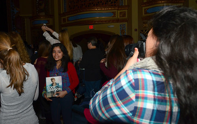 """Erica Benson-ebenson@shawmedia.com Cody Simpson fans (right) Valeria Alvarado of Bolingbrook takes photograph of her sister Rebecca with his book """"Welcome to Paradise: My Journey"""" during his performance at the Tivoli Theatre Tuesday October 22 2013."""