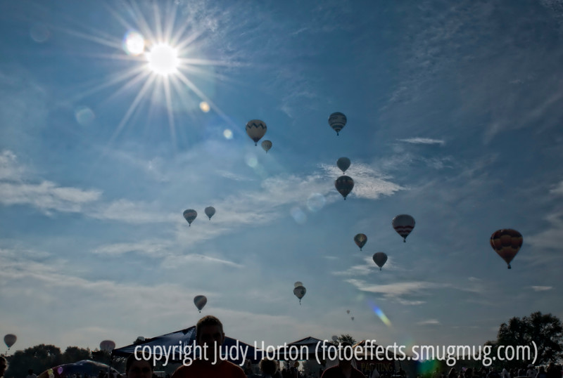 As a large group of hot air balloons in the Colorado Balloon Classic begin to move toward a landing spot, people from the festival are heading home.