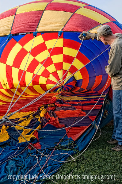 A man holds one of the hot air balloons up as it is being cool inflated at the Colorado Balloon Classic.