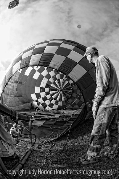 Cool inflating a hot air balloon at the Colorado Balloon Classic, 2009.  Several other balloon have ascended and one is in the clouds a bit.