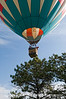 A hot air balloon skims by very close to some trees as it approaches for a a landing.