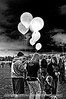 A mother buys a balloon for a small girl at the Colorado Balloon Classic in the early dawn.
