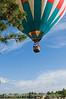 A hot air balloon approaches its landing spot