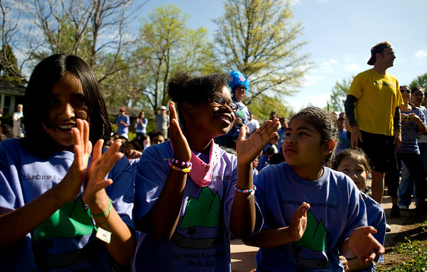 Kyky Bennett, 9, (center) Eileen Longoria, 10, (left) and Angela Ramires, 10, clap during the speeches before the annual Mile Marathon at Columbine Elementary School in Boulder, Friday, May 21, 2010. Elite athletes, teachers, students, and parents joined in the race that follows one mile of the Bolder Boulder course. <br /> <br /> Kasia Broussalian