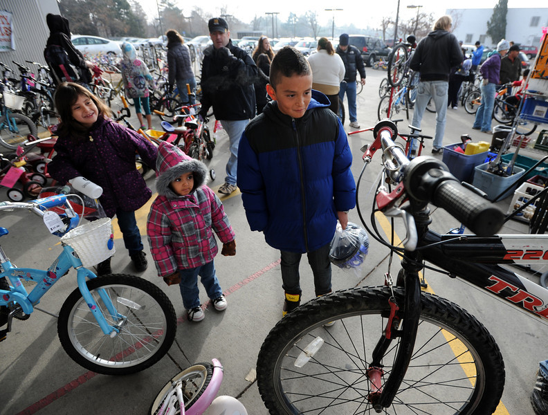 "Samantha Arellano, left,  her sister, Rosalinda, and brother, Emanuel, wait for their new bikes to be checked out by mechanics.<br /> Community Cycles hosted their 7th annual Kids' Holiday Bike Giveaway on Sunday.<br /> For more photos and a video of the bike giveaway, go to  <a href=""http://www.dailycamera.com"">http://www.dailycamera.com</a>.<br /> Cliff Grassmick  / December 16, 2012"