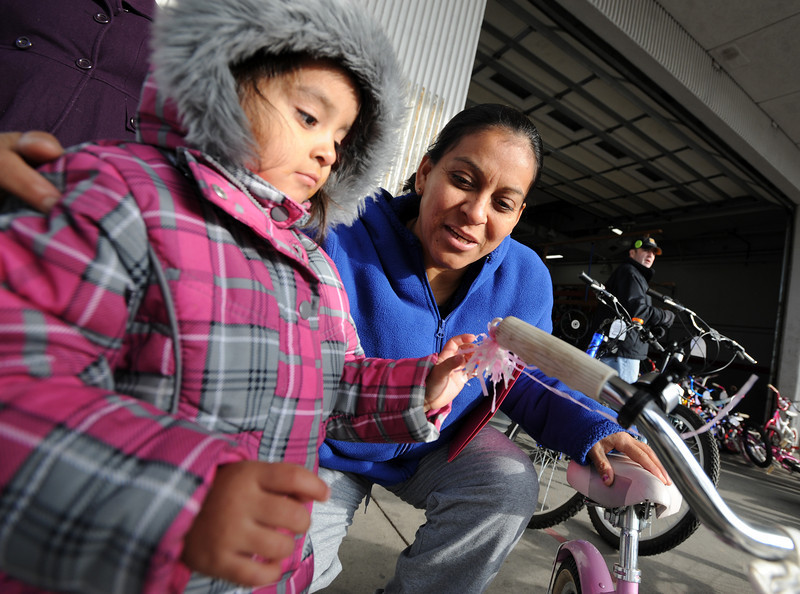 "Rosalinda Arellano, 4, waits to get on her new bike for the first time as her mother, Rosa, helps out.<br /> Community Cycles hosted their 7th annual Kids' Holiday Bike Giveaway on Sunday.<br /> For more photos and a video of the bike giveaway, go to  <a href=""http://www.dailycamera.com"">http://www.dailycamera.com</a>.<br /> Cliff Grassmick  / December 16, 2012"