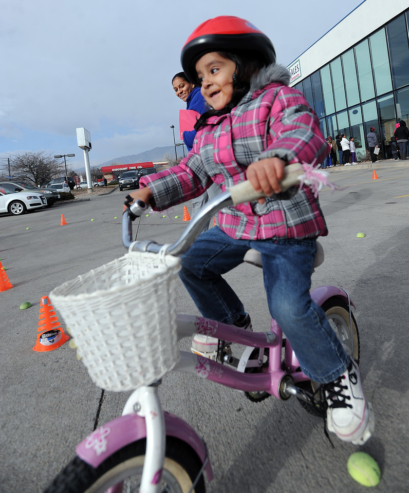 "Rosalinda Arellano, 4, rides her new bike for the first time as her mother, Rosa, watches in the background.<br /> Community Cycles hosted their 7th annual Kids' Holiday Bike Giveaway on Sunday.<br /> For more photos and a video of the bike giveaway, go to  <a href=""http://www.dailycamera.com"">http://www.dailycamera.com</a>.<br /> Cliff Grassmick  / December 16, 2012"
