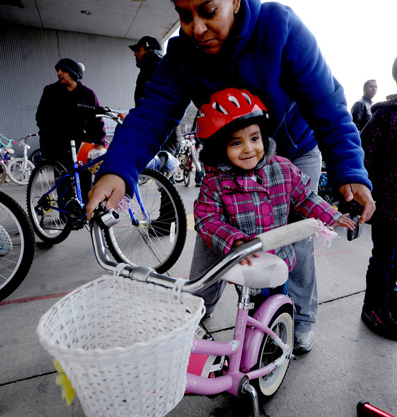 "Rosalinda Arellano, 4, gets on her new bike for the first time as her mother, Rosa, helps her get on.<br /> Community Cycles hosted their 7th annual Kids' Holiday Bike Giveaway on Sunday.<br /> For more photos and a video of the bike giveaway, go to  <a href=""http://www.dailycamera.com"">http://www.dailycamera.com</a>.<br /> Cliff Grassmick  / December 16, 2012"