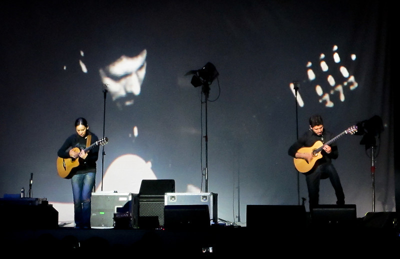 RYG performs with an image of Rodrigo in the background.