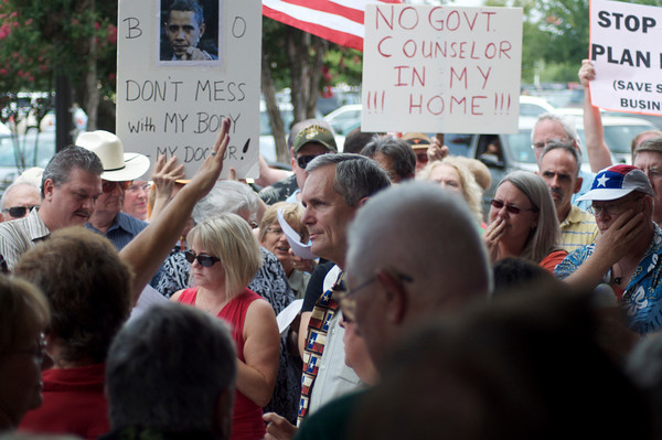 Some of Congressman Doggett's employees worked with the crowd trying to keep the volume of the heckling down. In this picture, the congressman is listening to a question from one person in the crowd while several others are shouting at him. The extended hand on the left side of the picture belongs to a woman who is trying to silence the angry people in the crowd.