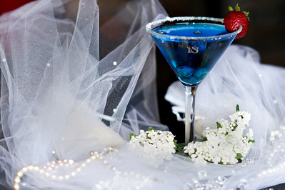 "The Bride  - ""Bride IS""  1.5 oz. ISVodka  1 oz Blueberry Schnapps  .5 oz Blue Curacao 3 Blueberries 1 Strawberry  Add ISVodka, Blueberry Schnapps and Blue Curacao to ice-filled shaker... shake well.  Rim a martini glass with sugar.  Now pour.  Add blueberries and strawberry.  Photograph by Mark Bowers. Set-up and props by Kiki Kalor."