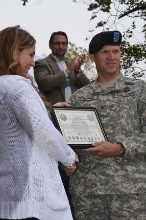 SFC Combat Medic Micah Welintukonis, who was severely injured while on active duty in Afghanistan, receives the Purple Heart Award at the conclusion of the parade. His wife Camilla was also presented with a special citation acknowleging her bravery during the many challenges her family faced during this time.