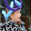 A spectator enjoys the parade - and her balloon hat.