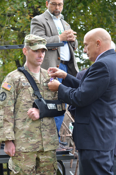 SFC Combat Medic Micah Welintukonis, who was severely injured while on active duty in Afghanistan, receives the Purple Heart Award at the conclusion of the parade.