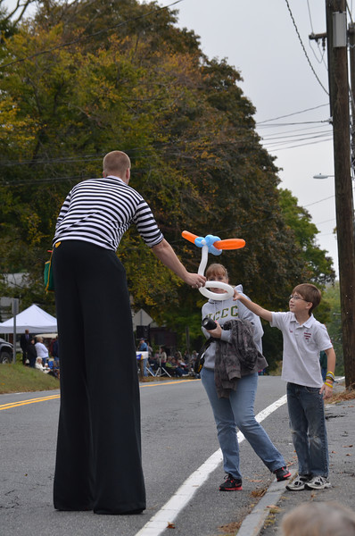 Stilt-walkers entertain the crowd while waiting for the parade to start.