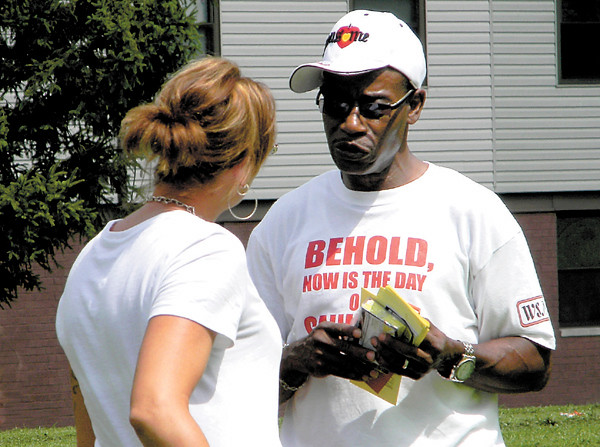 Dan Irwin/NEWS<br /> Minister Lee Riddle, holding tracts that explain the Bible's message of salvation, talks with a young woman during Saturday's multi-church outreach at Crestview Gardens.