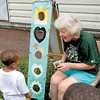 The Rev. Hope Cummins of Wayside Emmanuel Church explains a gospel-themed toss game to a young participant. — Dan Irwin
