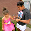 Ariana Mitteff of Vision Ministries paints the arm of a child during the Crestview Gardens outreach. — Dan Irwin