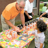 Dan Irwin/NEWS<br /> J.R. McFarland gives a child's New Testatment to a youngster during Saturday's multi-church outreach at Crestview Gardens. McFarland and Bob Shaffer, rear, both are local members of Gideons International.