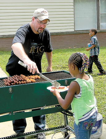 Dan Irwin/NEWS<br /> The Rev. Albert Librizzi, pastor of Barnstone Ministries, presents a hot dog to a young girl during Saturday's multi-church outreach at Crestview Gardens.