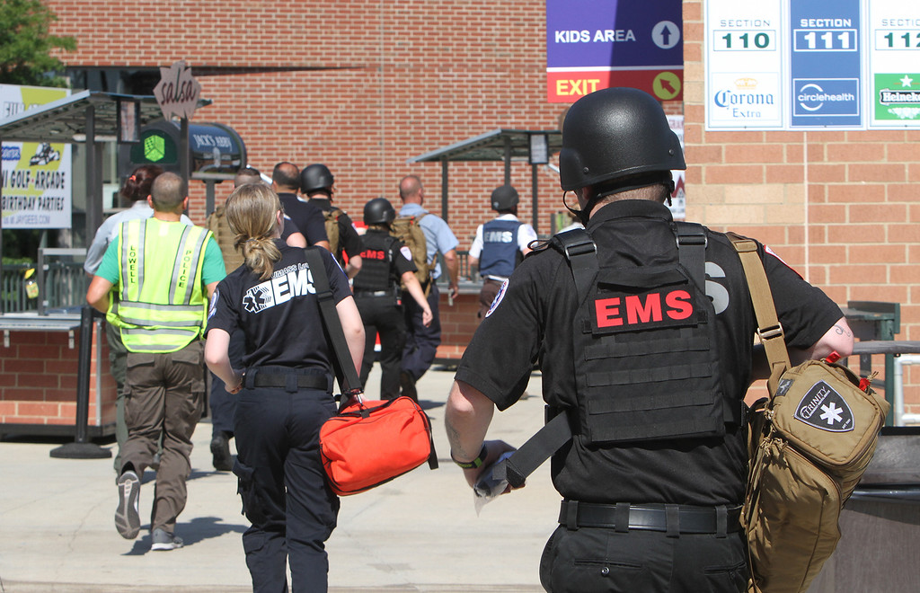 . Lowell Police, Fire, UMass Lowell Police, Trinity, LGH and UML EMS, and NEMLEC participate in critical event training at LeLacheur Park involving a simulated attack by gunmen. EMTs move in with protection when it\'s safe. (SUN/Julia Malakie)
