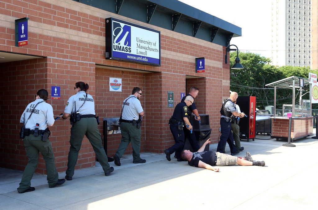 . Lowell Police, Fire, UMass Lowell Police, Trinity, LGH and UML EMS, and NEMLEC participate in critical event training at LeLacheur Park involving a simulated attack by gunmen. Victim points the way to bad guys. (SUN/Julia Malakie)