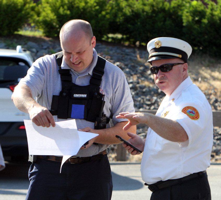 . Lowell Police, Fire, UMass Lowell Police, Trinity, LGH and UML EMS, and NEMLEC participate in critical event training at LeLacheur Park involving a simulated attack by gunmen. Lowell deputy fire chief Bill Charron, left, and fire chief Jeffrey Winward, right, prepare at staging area. (SUN/Julia Malakie)