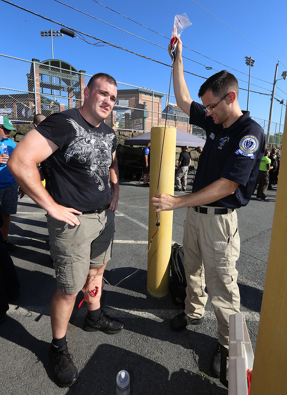 . Lowell Police, Fire, UMass Lowell Police, Trinity, LGH and UML EMS, and NEMLEC participate in critical event training at LeLacheur Park involving a simulated attack by gunmen. Lowell Police Academy trainee Max Regan of Lowell, left, waits as UML EMS field supervisor Nathan Roberts of Oakham, Mass., holds up a bag of fake blood to drain. (SUN/Julia Malakie)