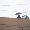 Record-Eagle/Jan-Michael Stump<br /> Fans try to stay dry while waiting in the stands over an hour before the start of Friday's game between Traverse City Central and Traverse City West at Thirlby Field.