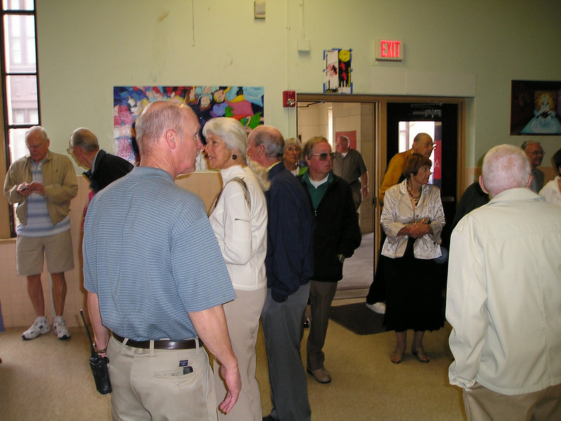 In the hallway outside the cafeteria, the Class of 1949 reunion tour passes through.