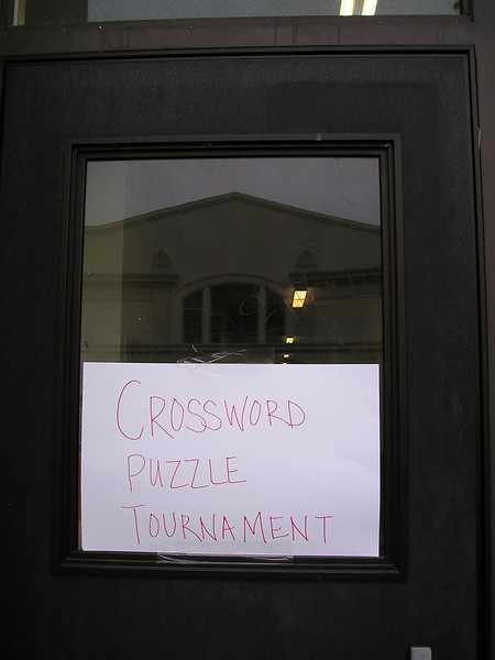 Crossword puzzle tournament sign on one outside door, with the lovely old church across the street reflected in the window.