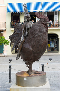 Every city needs a statue of a naked woman wearing high heels, riding a rooster and holding a giant fork.