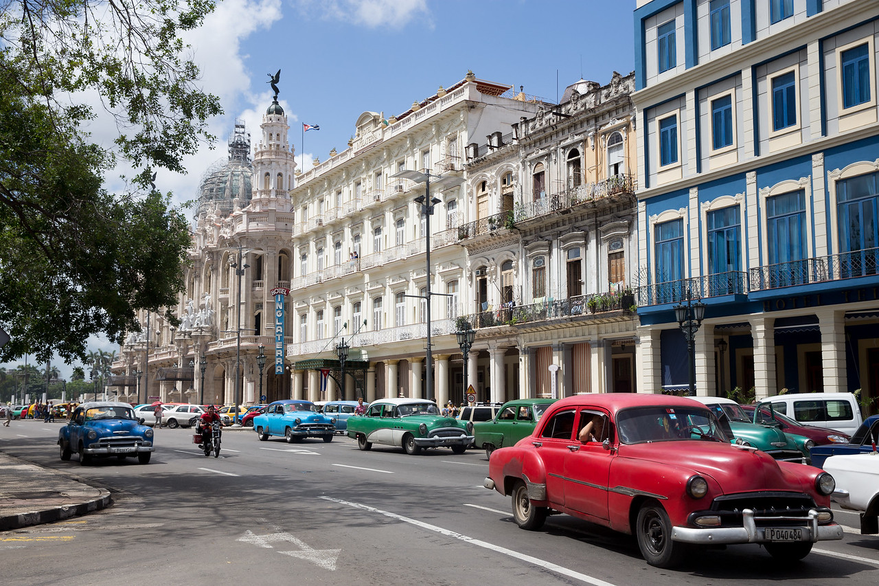 19. Cars pass by the Gran Teotro and Hotel Inglaterra on Prado street in Havana.