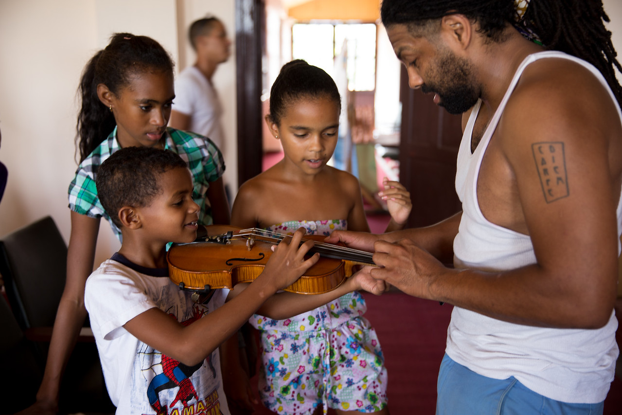 17. Seattle musician Ben Hunter shows children from Viñales, Cuba, how to play a violin at the cultural center.