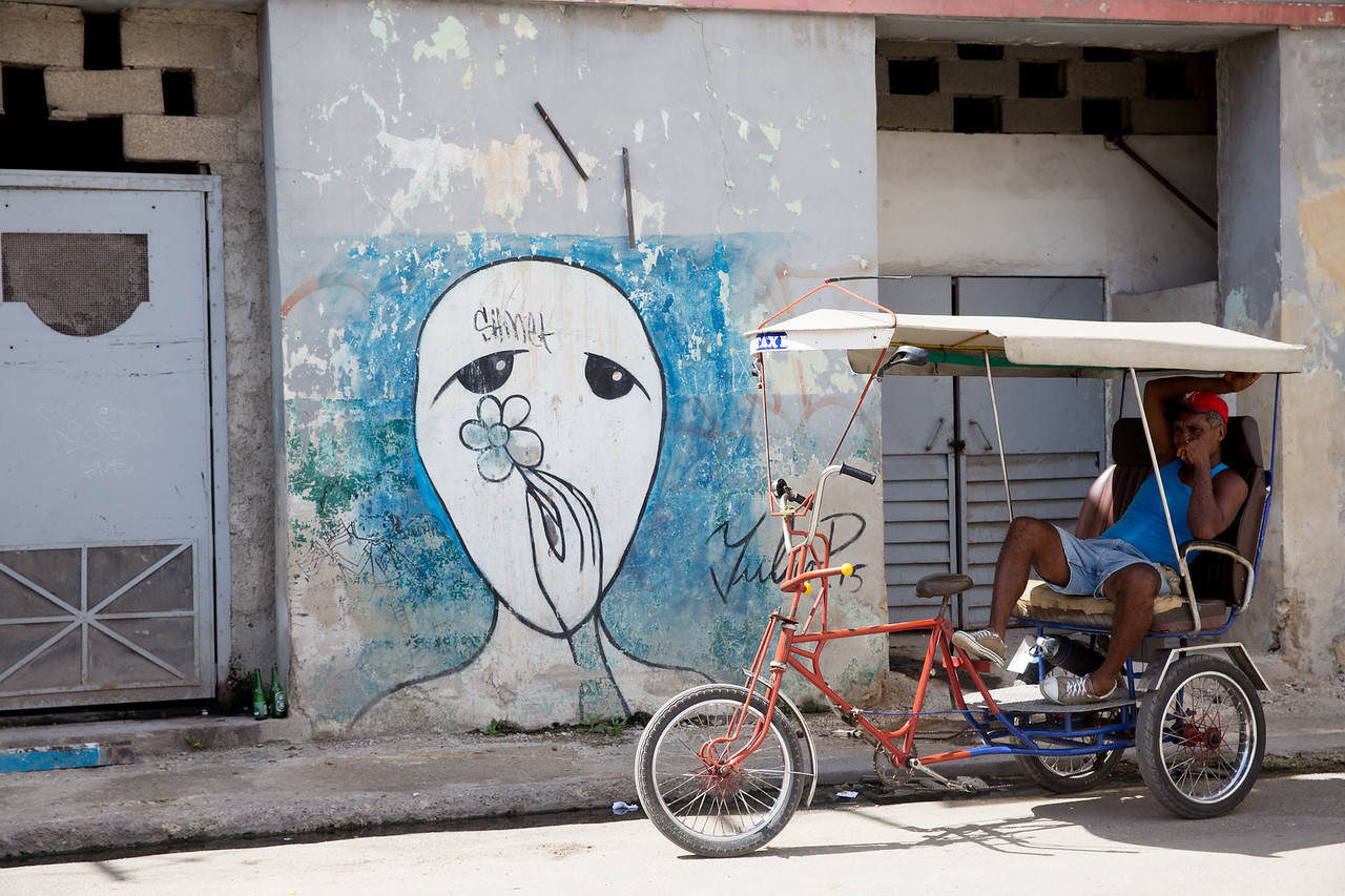 A bicycle taxi driver, or bicitaxi, waits for customers in front of street art by ubiquitous artist Yulier near Obispo Street in Havana.
