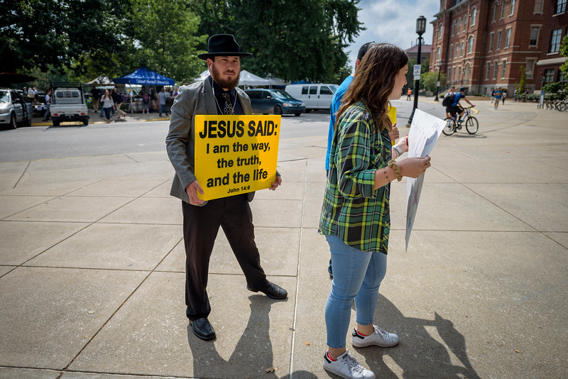 A cronie of Brother Jed, a radical evangelical Christian, is blocked by student protestors.