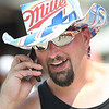 Mark Robinson of Rochester, NY keeps cool underneath his Miller Lite hat as he catches up on the phone and walks through Earnhardt Campgrounds and enjoys the vendors during race weekend at Bristol Motor Speedway. Photo by Erica Yoon