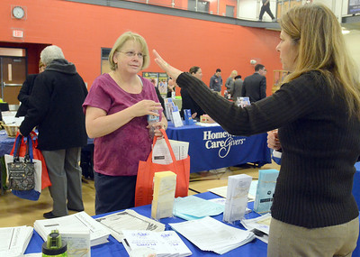 Erica Benson—ebenson@shawmedia.com  Joan Topel of Lemont learns about Plows Council on Aging from employee Christine Suddreth during the senior fair held at the CORE hosted by Congressman Dan Lipinski Monday Feb. 18 2013.