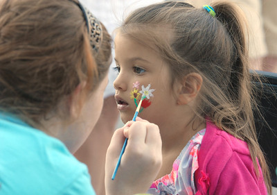 Erica Benson-ebenson@shawmedia.com Mia Echevarria of Naperville gets her face painted by Hannah Lindsey of Hinsdale during the annual Dancin' in the Street summer concert series in Clarendon Hills Wednesday, June 19 2013. The event is held through the village of Clarendon Hills.