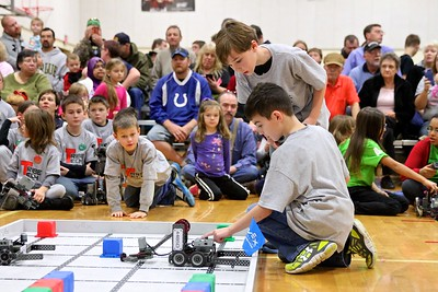 Carson Spurlock (kneeling) and Hayden King (standing) power up their robot before the start of competition.